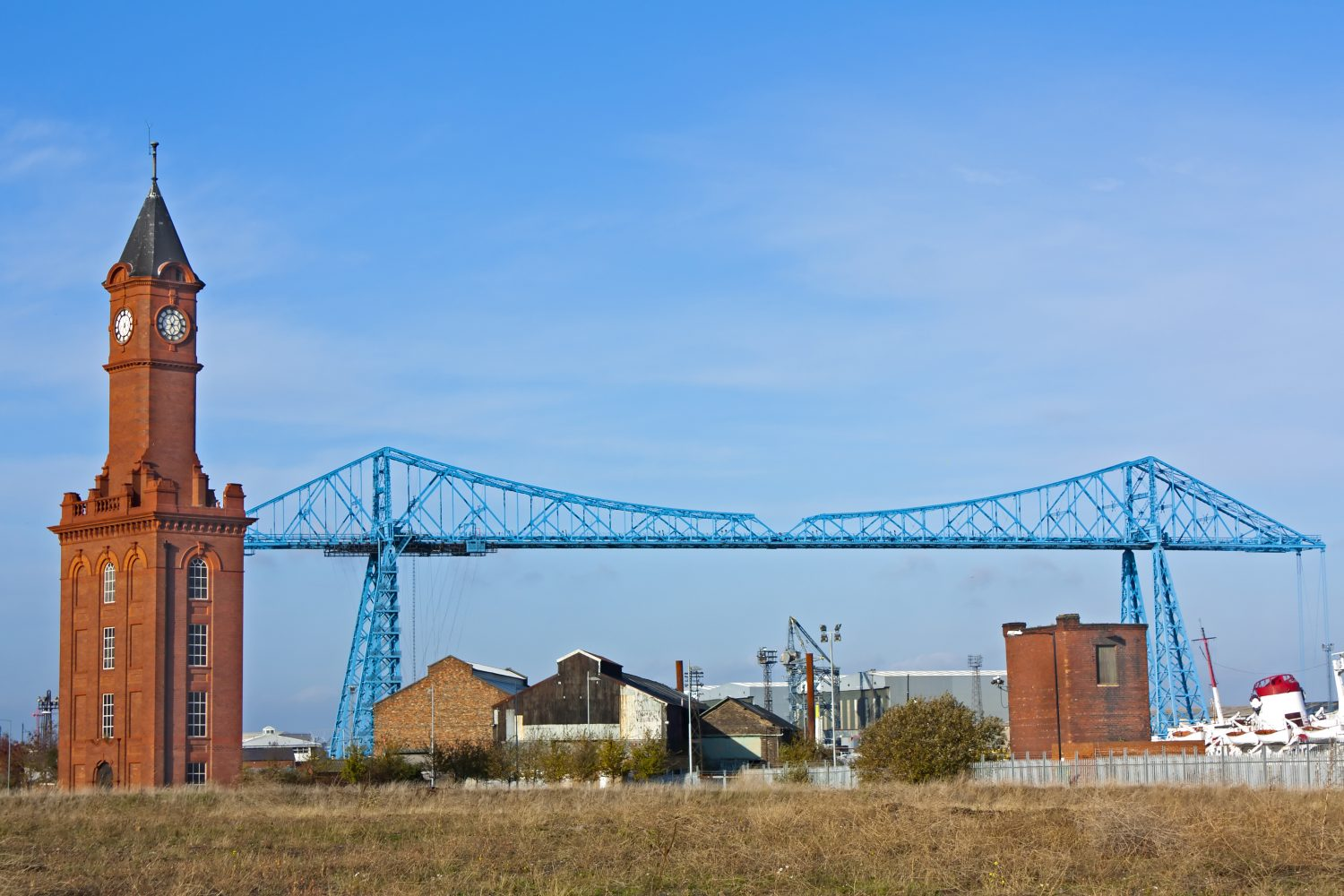 Landscape scene including a tower and blue industrial bridge.