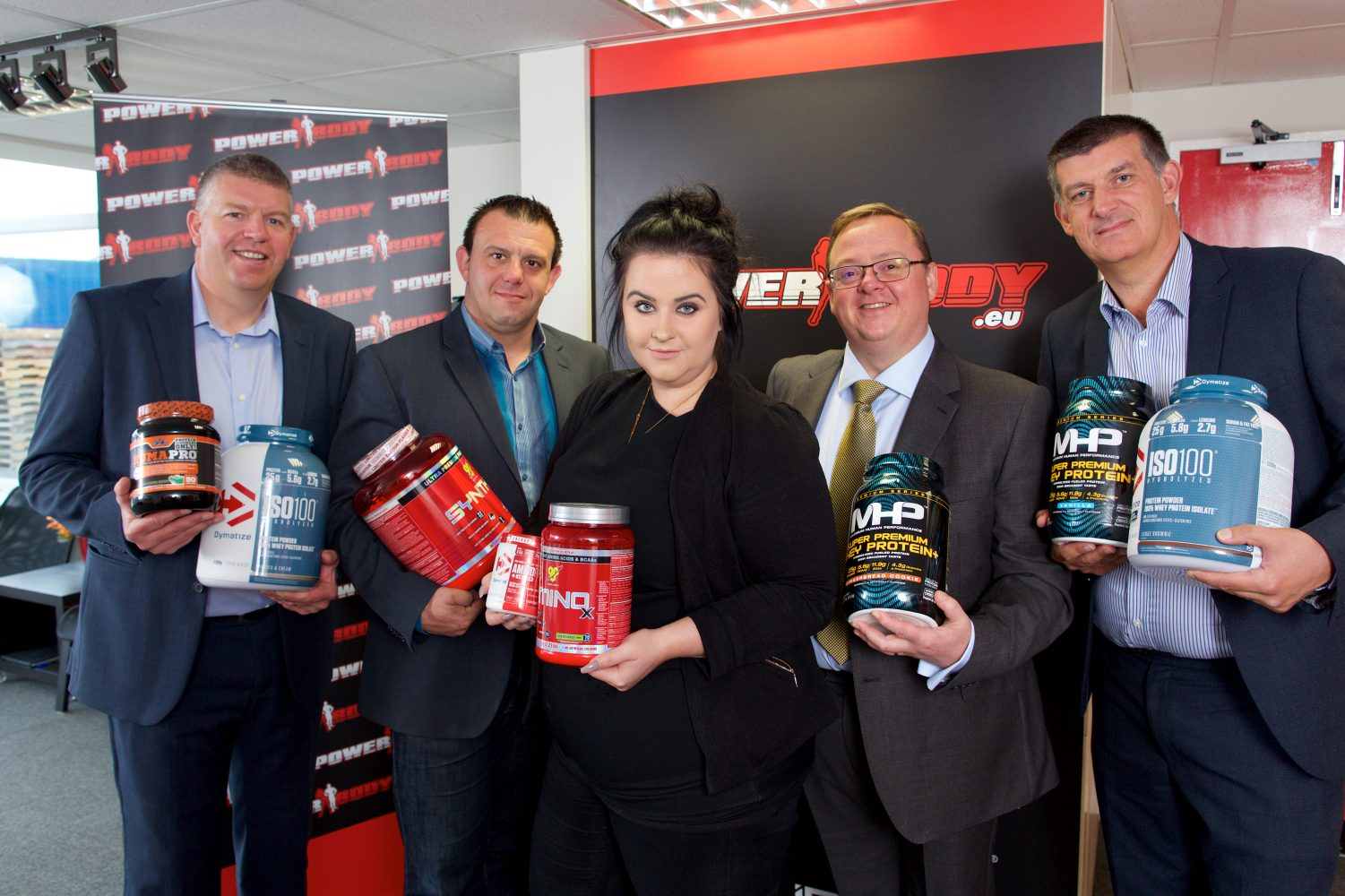 Four men and a woman holding large plastic canisters of product in an office.