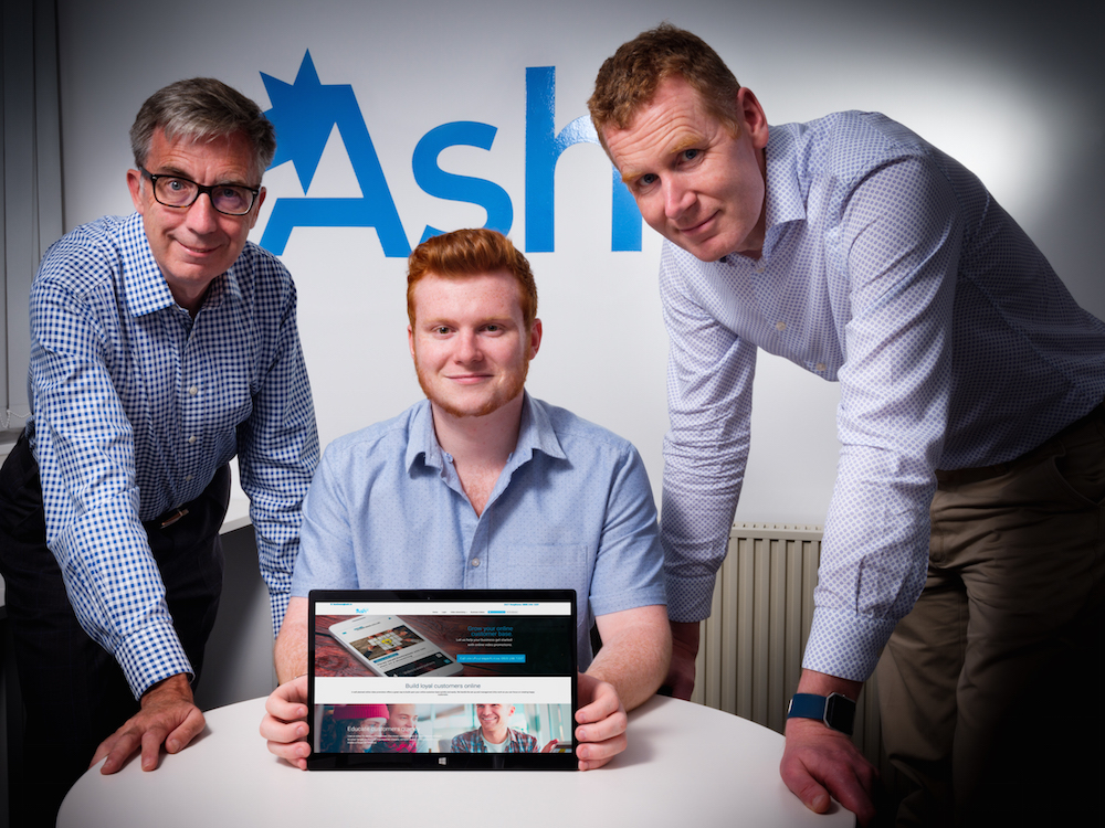 3 men from Ash TV gathered around a table showing an Ipad with their website displayed