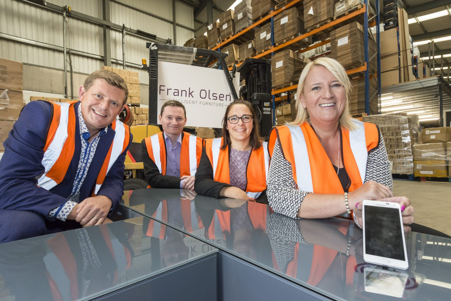Four women standing in a factory with Frank Olsen signage behind them. They are all wearing high vis jackets. There are two women in the group and the woman to the far right has blonde hair and standing next to her is a woman with dark hair wearing glasses.
