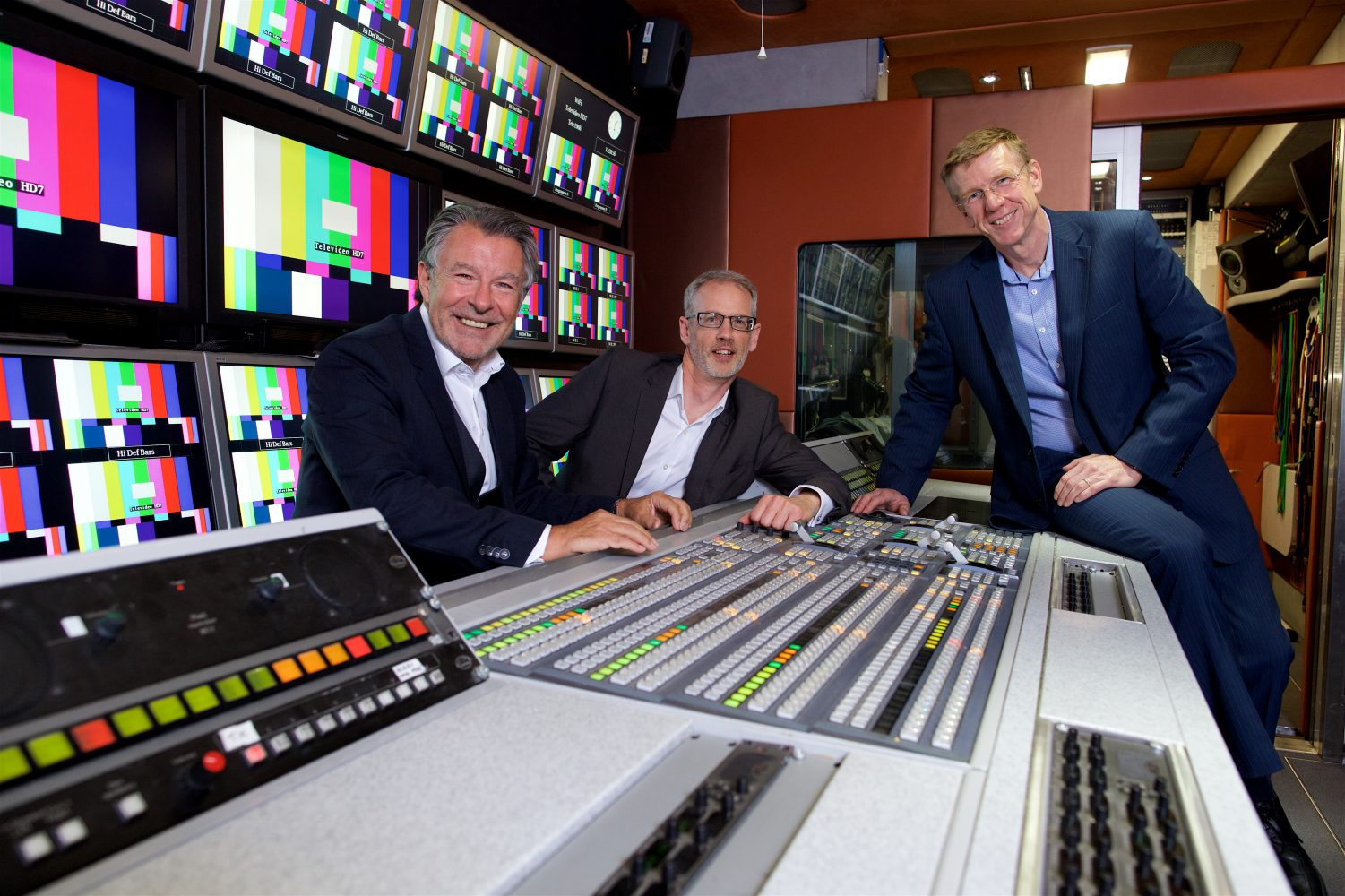3 men in suits from Televido sat in a broadcasting room