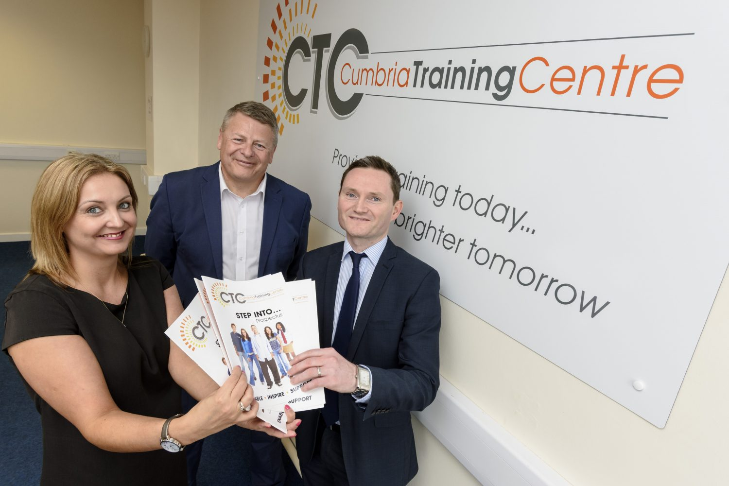 Three people in an office standing near a wall with a poster of CTC Cumbria Training Centre poster. There is one woman to the far let with light brown hair wearing a black tee shirt holding some brochures and another man to the far right wearing a blue suit and blue tie also holding the brochures.