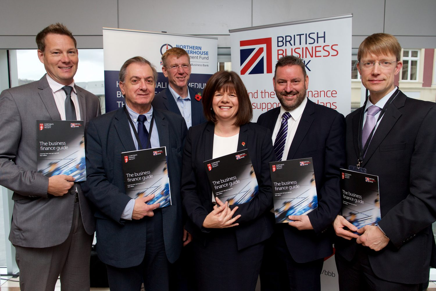 Five suited men and a woman standing around point of sale holding brochures in an office.