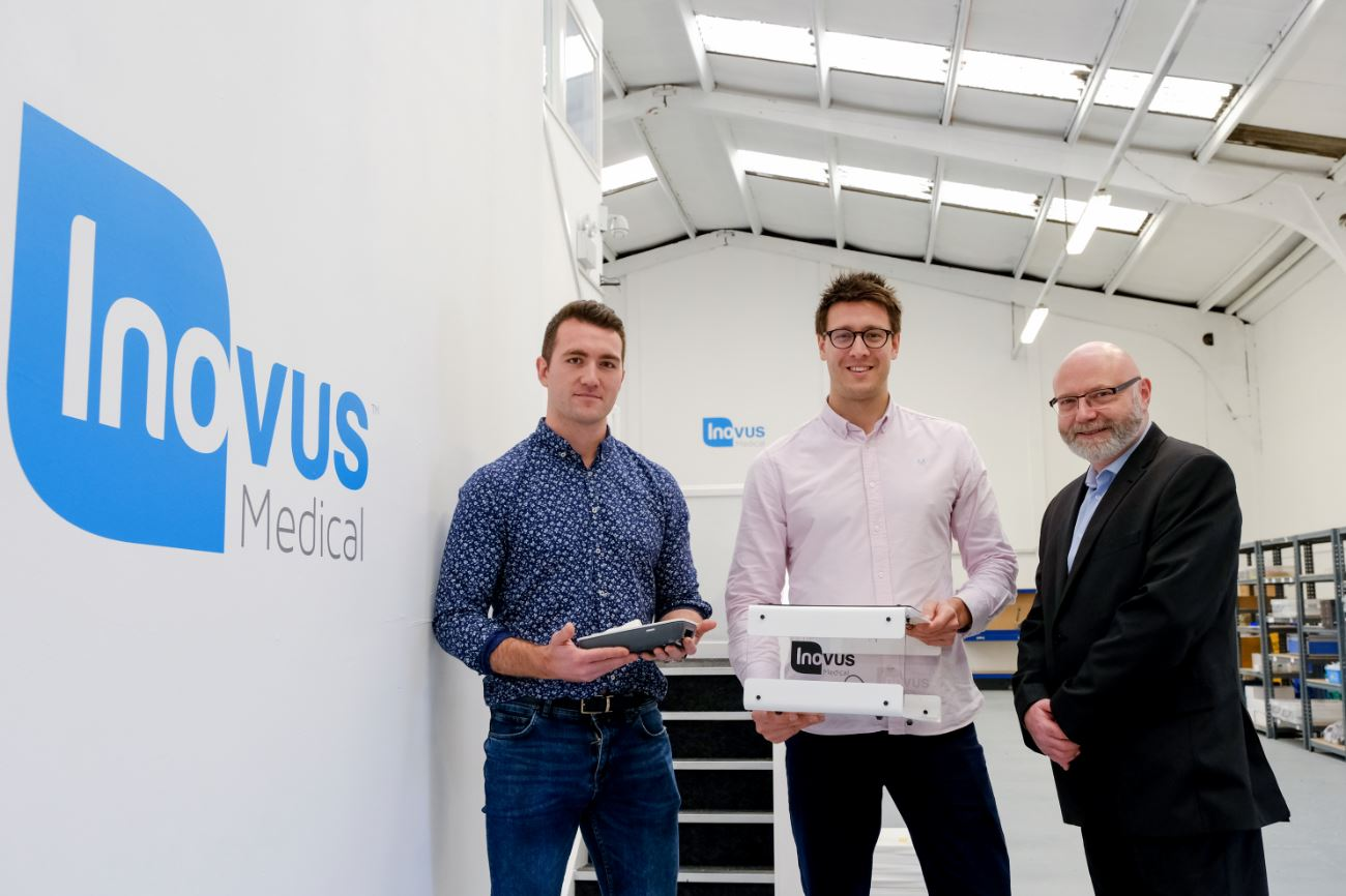 3 men from Inovus Medical stood in their warehouse holding some equipment