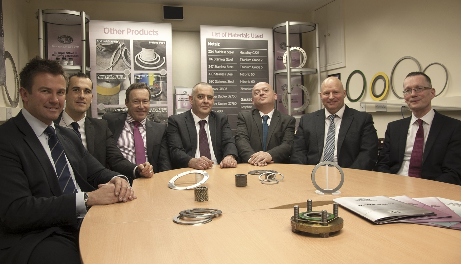 Seven suited men sitting around an oval table surrounded by industrial products on the table and point of sale behind them.