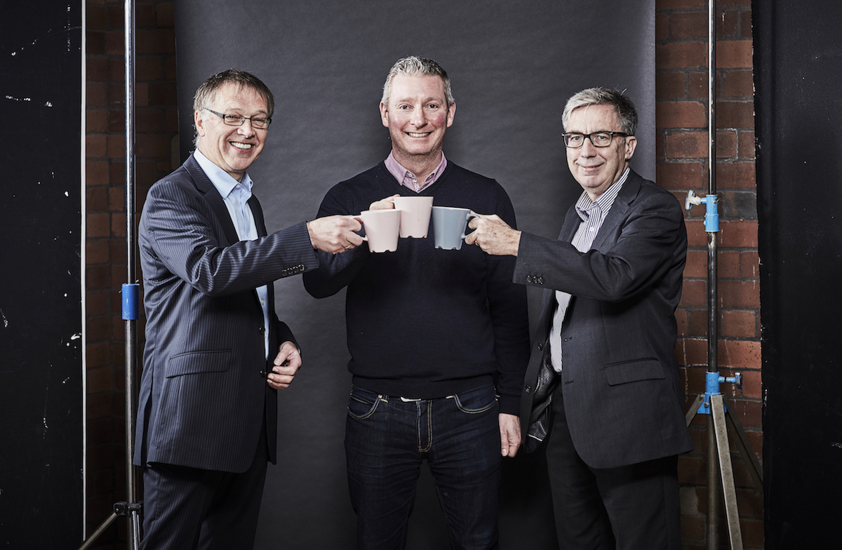 Three men in an office all handing mugs standing behind a brick wall.