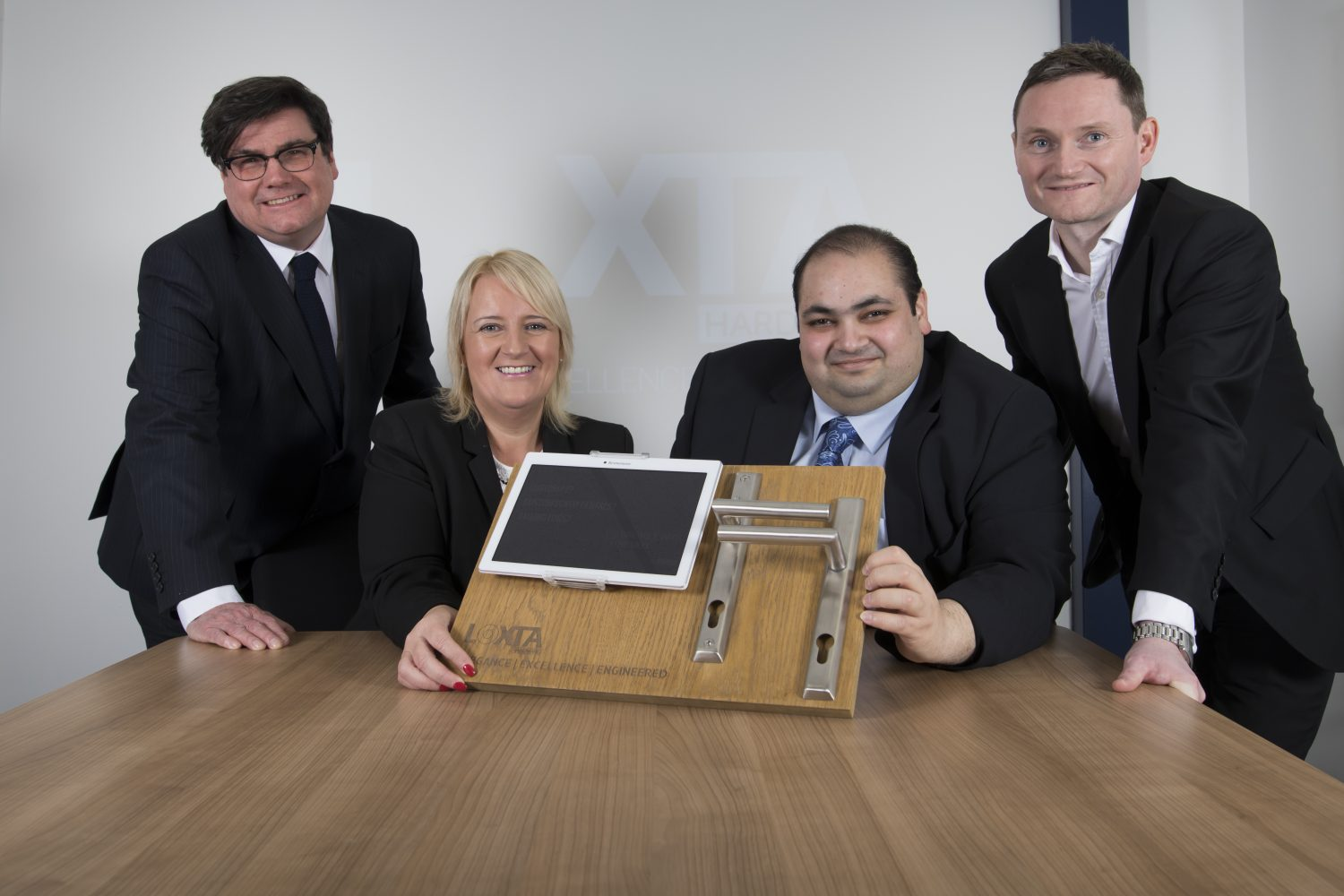 Four people around a desk. Man to the far right is wearing a black suit is standing, next to him is a seated man with his hand holding some equipment. There is a blond haired woman also holding the equipment. To the far left is man standing wearing glasses and a black tie.