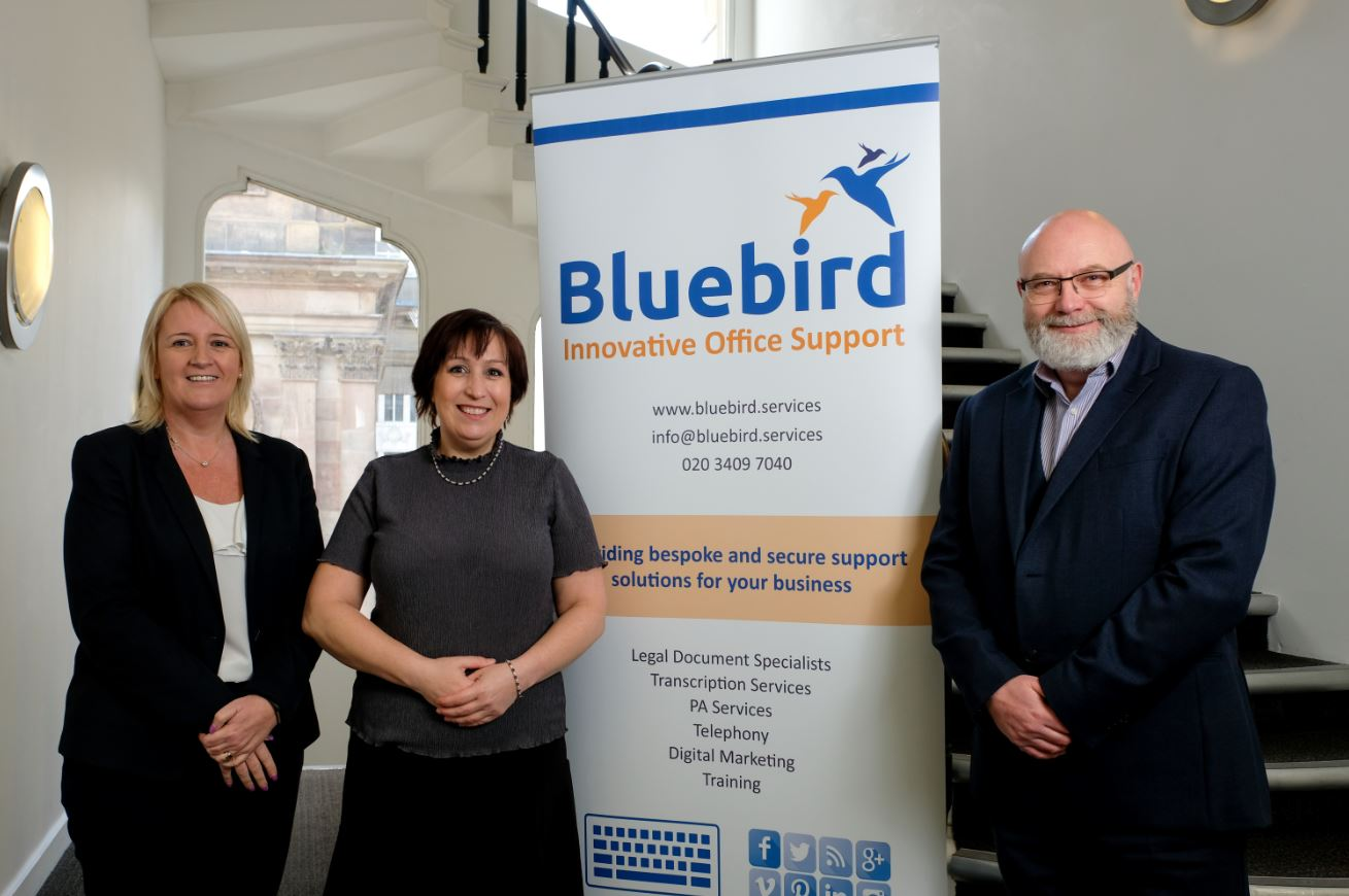 Two women and a man standing alongside a large poster stating Bluebird Innovative Office Support.