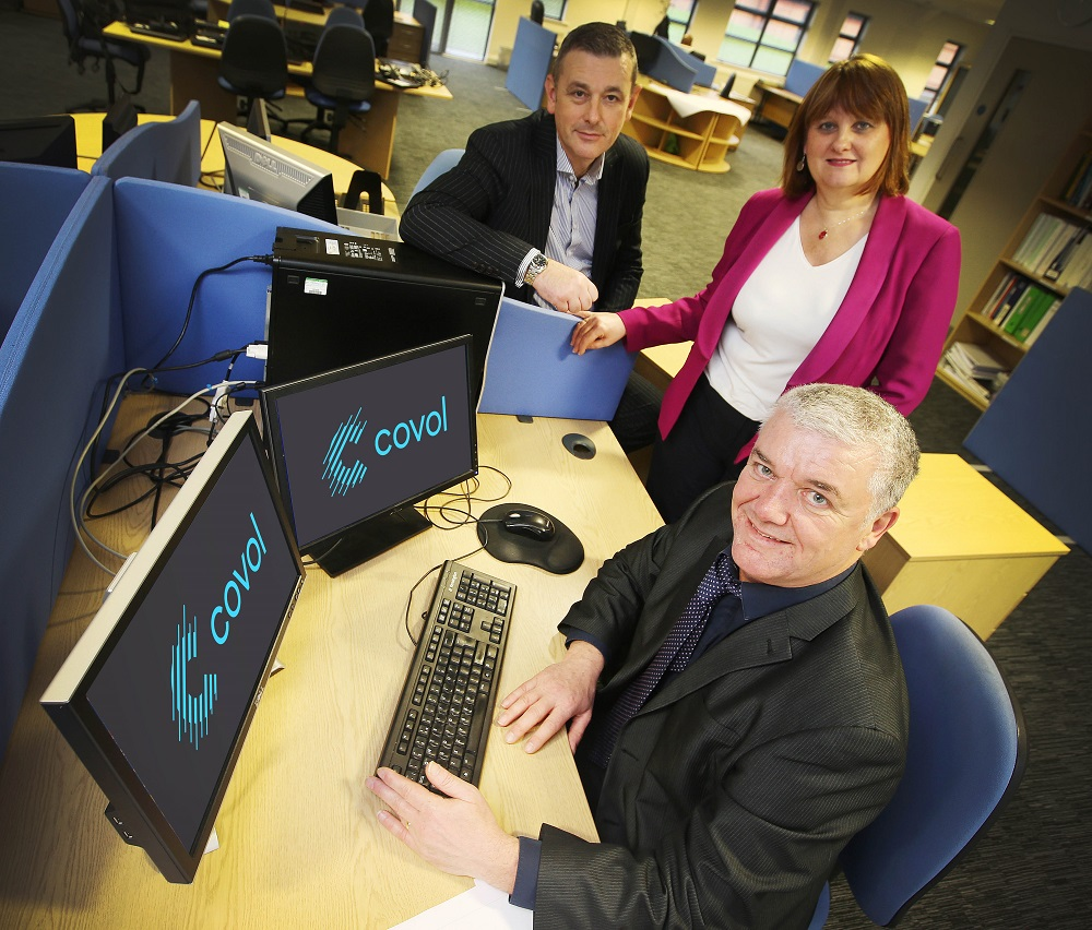 One business man sitting at a desk in front of two computer screens with Covol branding on it. There is a woman and man standing around the desk.