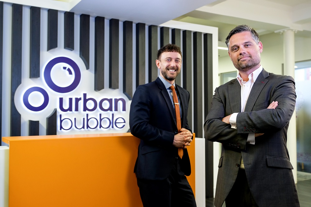 Two business suited men standing in front of an orange painted desk with Urban bubble branding on the wall behind them.