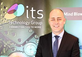 Man in suit in front of ITS Technology Group branding on the wall.
