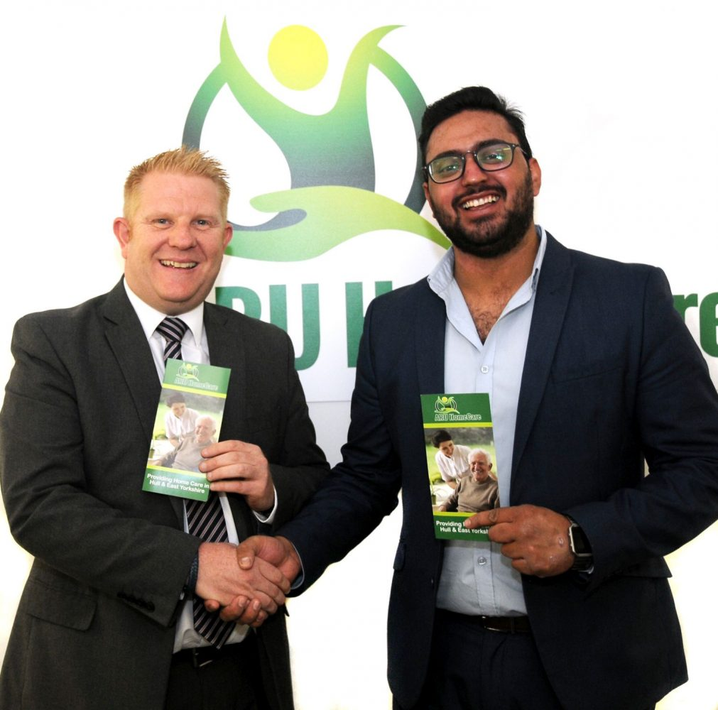 Two men holding leaflets shaking hands standing in front of Aru branding.