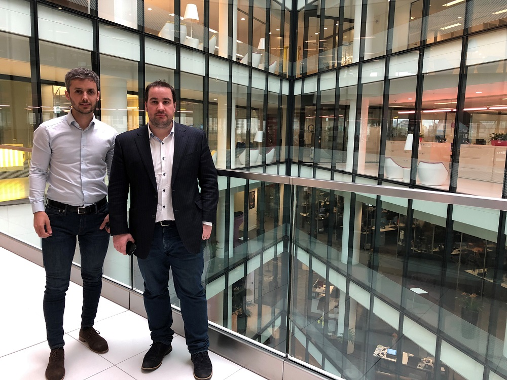 Two businessmen standing in an office building. They are in front of a large glass wall.