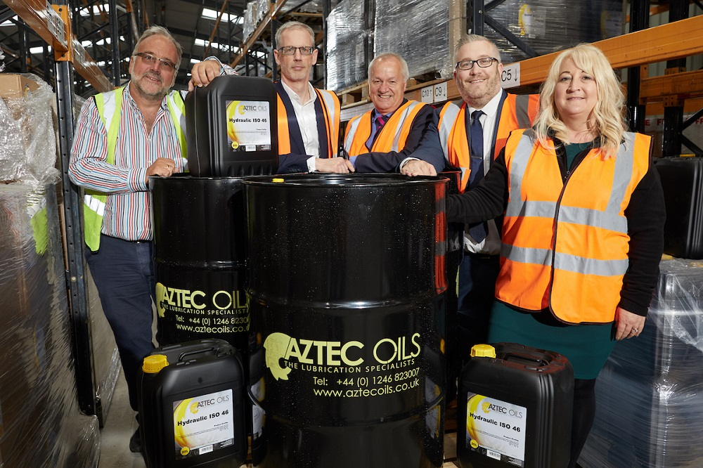 Five people in a factory standing next to Aztec Oils drums. One woman and four men are wearing Hi Vis jackets.