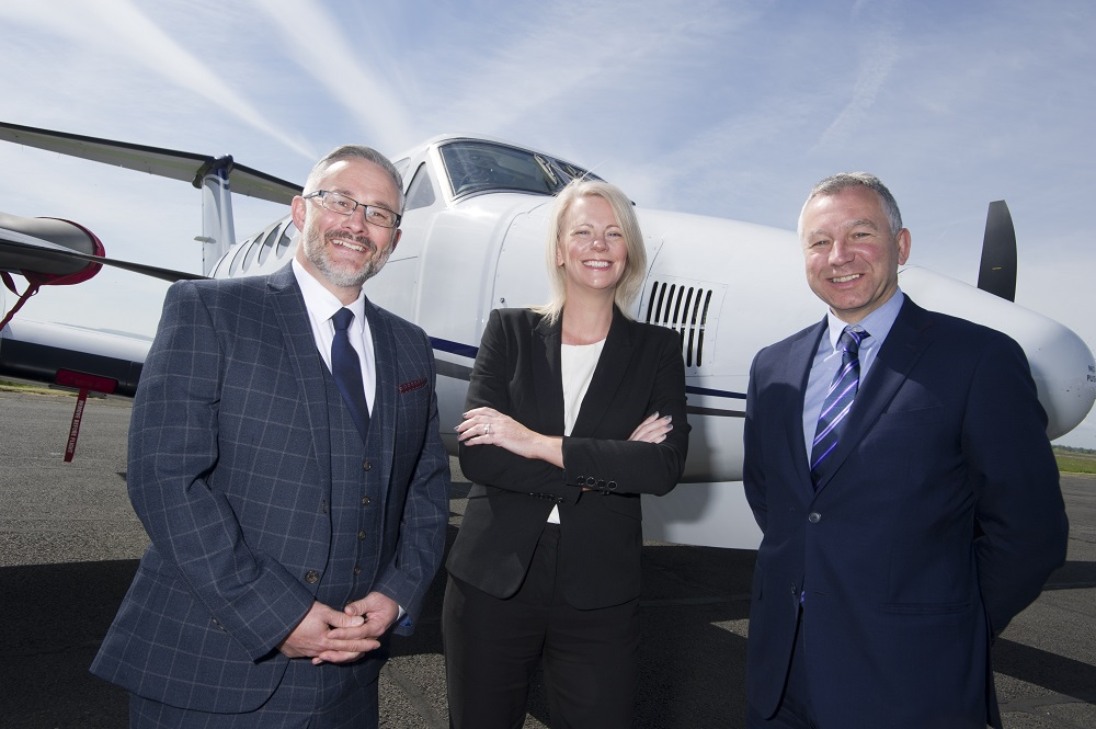 Two businessmen and business woman in the middle of the group standing in front of a small private aeroplane.