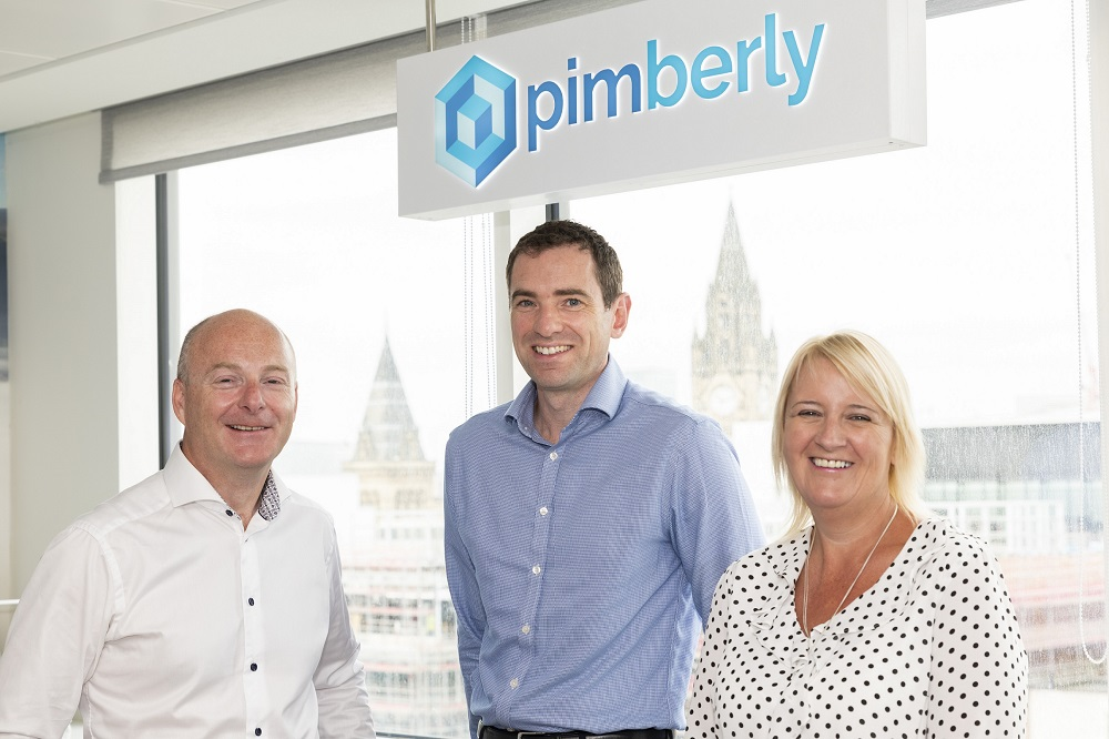 Three people in an office standing in front of a window with signage stating Pimberly. The woman to the far right is wearing a white and black spotted top and has blond hair. The man in the middle is wearing a blue shirt and the man to the far left is wearing a white shirt.