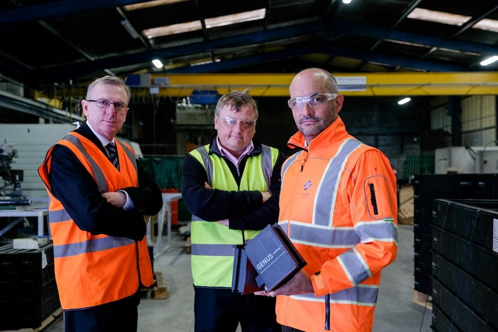 Two men in orange Hi Vis and a man in the middle of the row wearing yellow Hi Vis. There are situated in a factory.