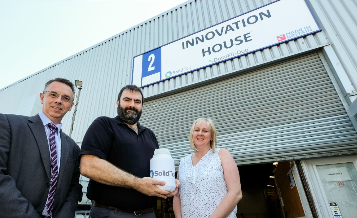 Two men and a woman with blonde hair standing outside office named Innovation House. Man in the middle of the group holding a plastic canister with Solid Tek on it.