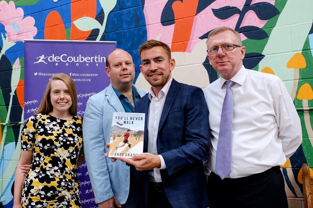 Three men and one woman in a colourful dress standing in front of a colourful brick wall. Man in the middle of the row of people is holding a book called 'You'll New Walk'.
