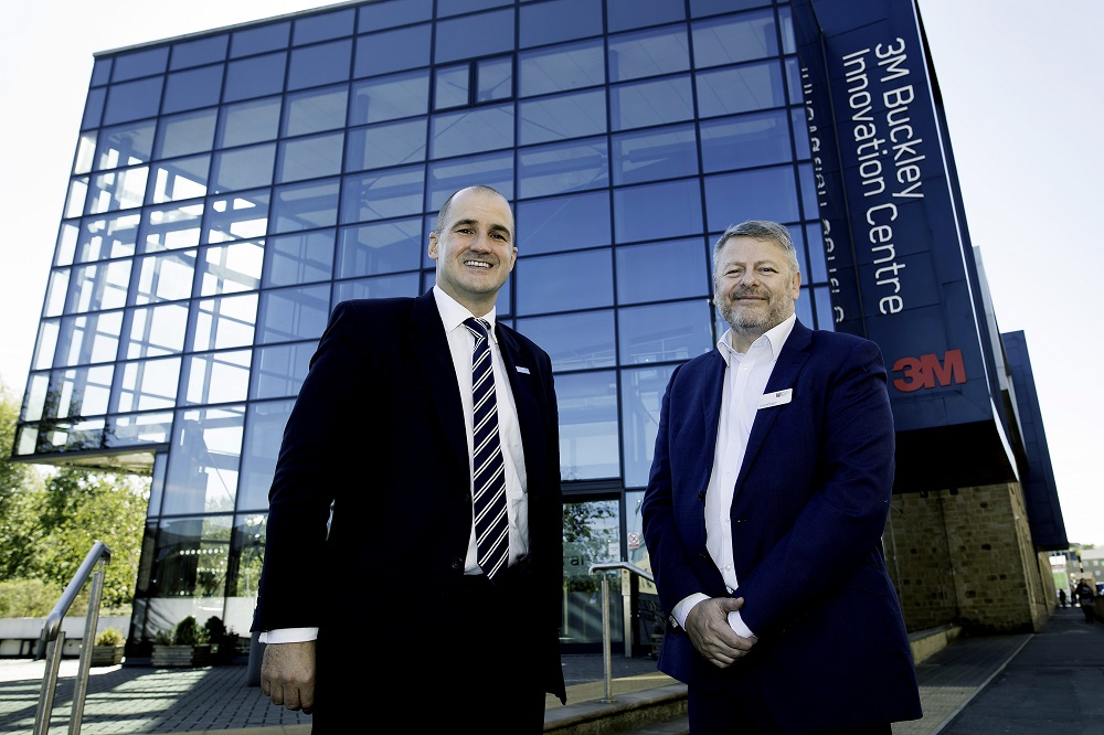 Two men standing outside the 3M Buckley Innovation Centre. Man to the right has grey hair and is wearing a blue suit with a white shirt and the other man is nearly bald and is wearing a black suit, white shirt and blue stripey tie.