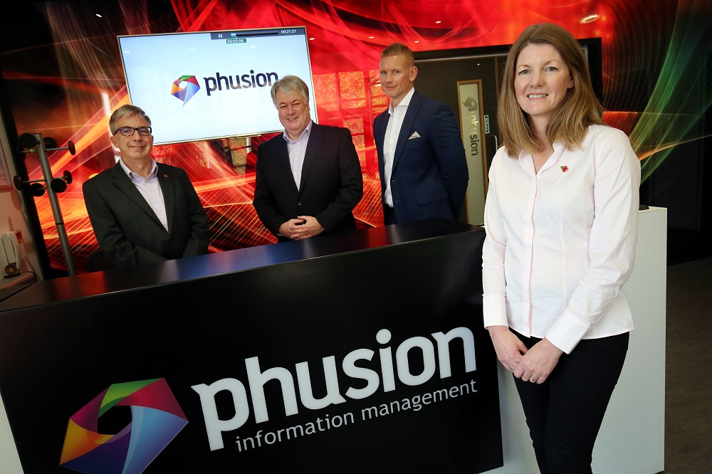 Three men wearing black suits and a woman wearing white shirt and black trousers standing in a room with Phusion Information Management point of sale.