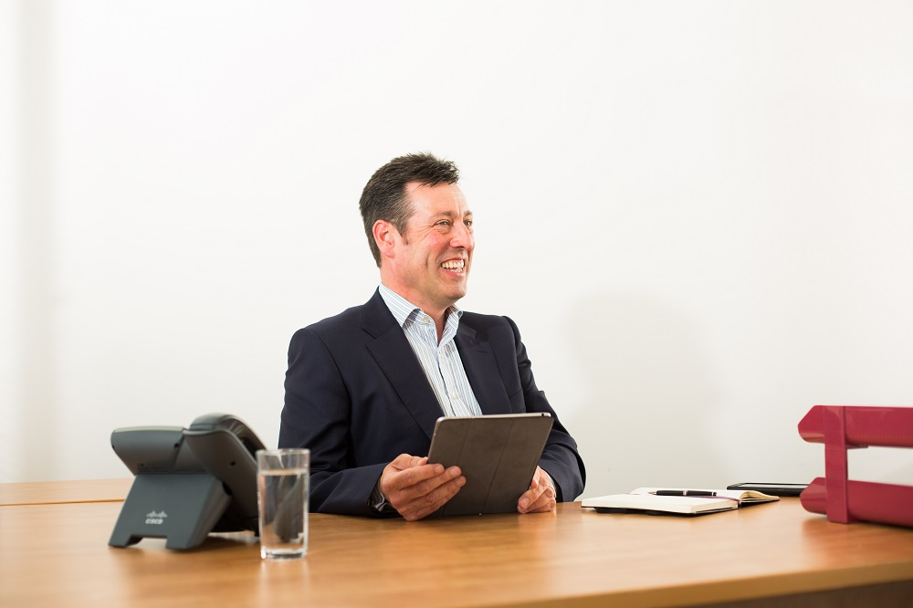 Will Clark, the Equity Fund Principal at Mercia sat a desk holding an iPad and laughing