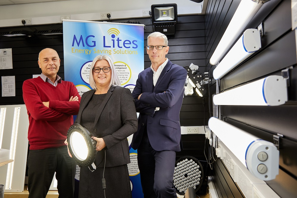 One man wearing a red jumper, woman wearing a brown suit and man with navy blue suit standing in front of MG Lites signage.