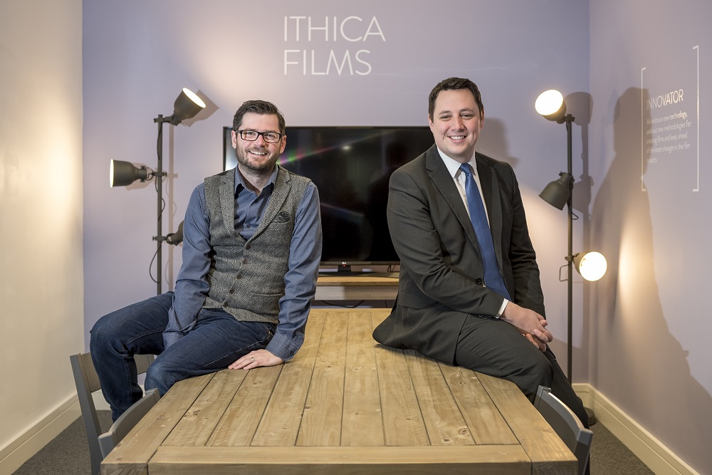 Two men sitting on a pine table with a purple wall with Ithica Films signage on it.