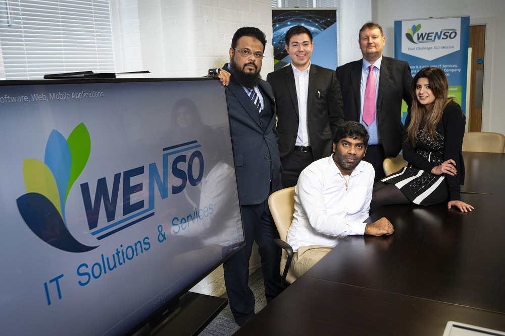 4 men and a woman sat in a meeting room with Wenso IT Solutions and Services TV Screen and pop up banner
