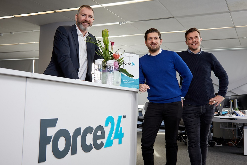 Three men in an office. One man standing behind a workstation with Force24 written on it.