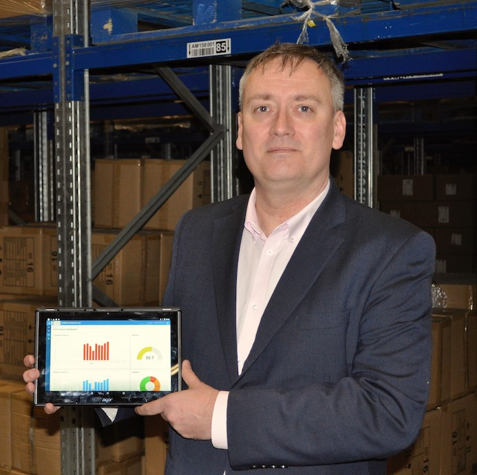 Gareth Dodd, chief technology office at OMS, holding a tablet whose display shows the company's software product