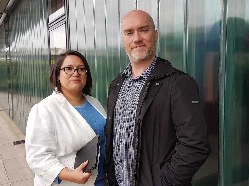 Man and woman outside green industrial building. Woman wearing glasses and has dark shoulder length hair to the left of the man is wearing a white jacket and a light blue top.