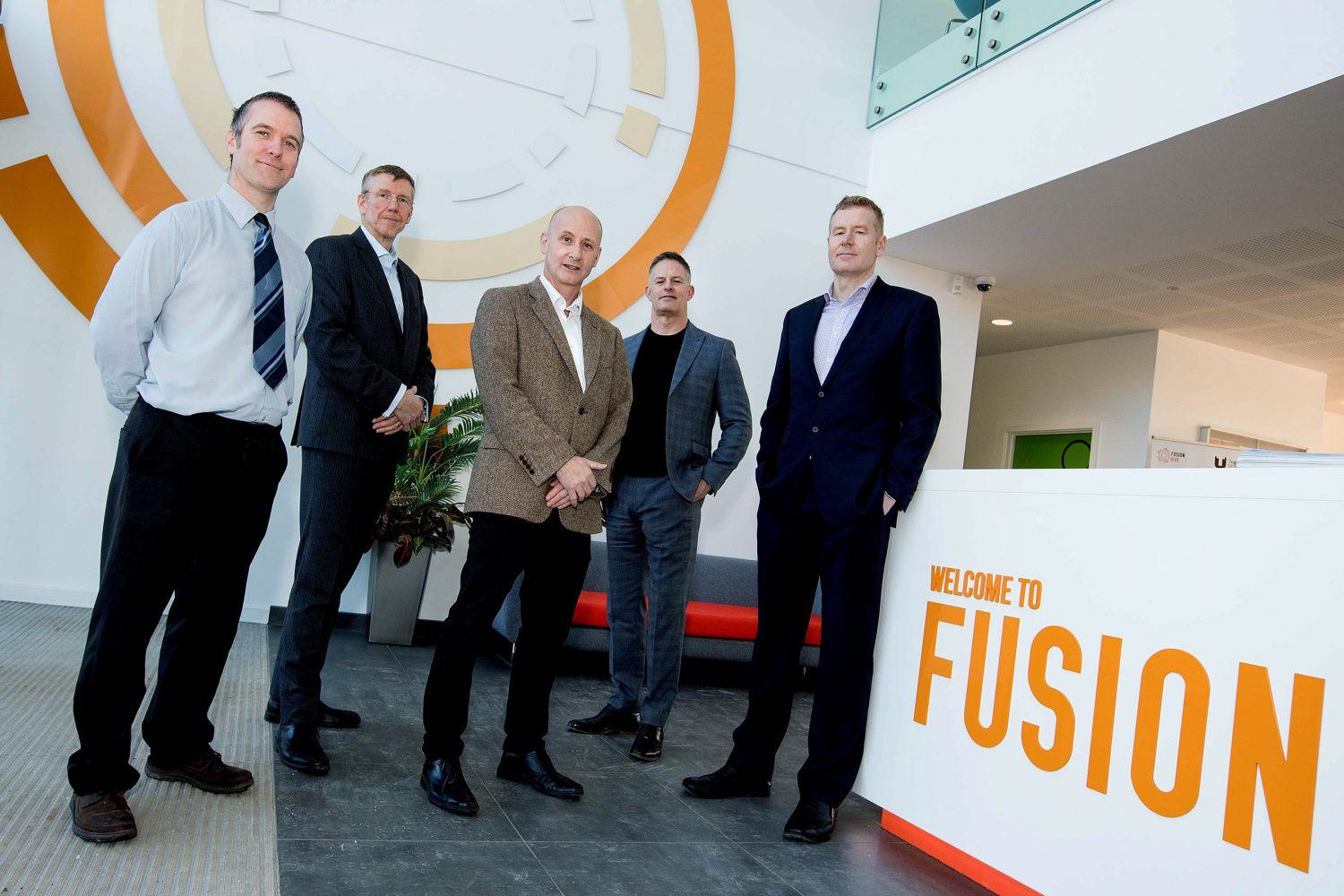 Five men standing, man to far right wearing a black suit is standing against a reception desk with Welcome to Fusion signage on it.