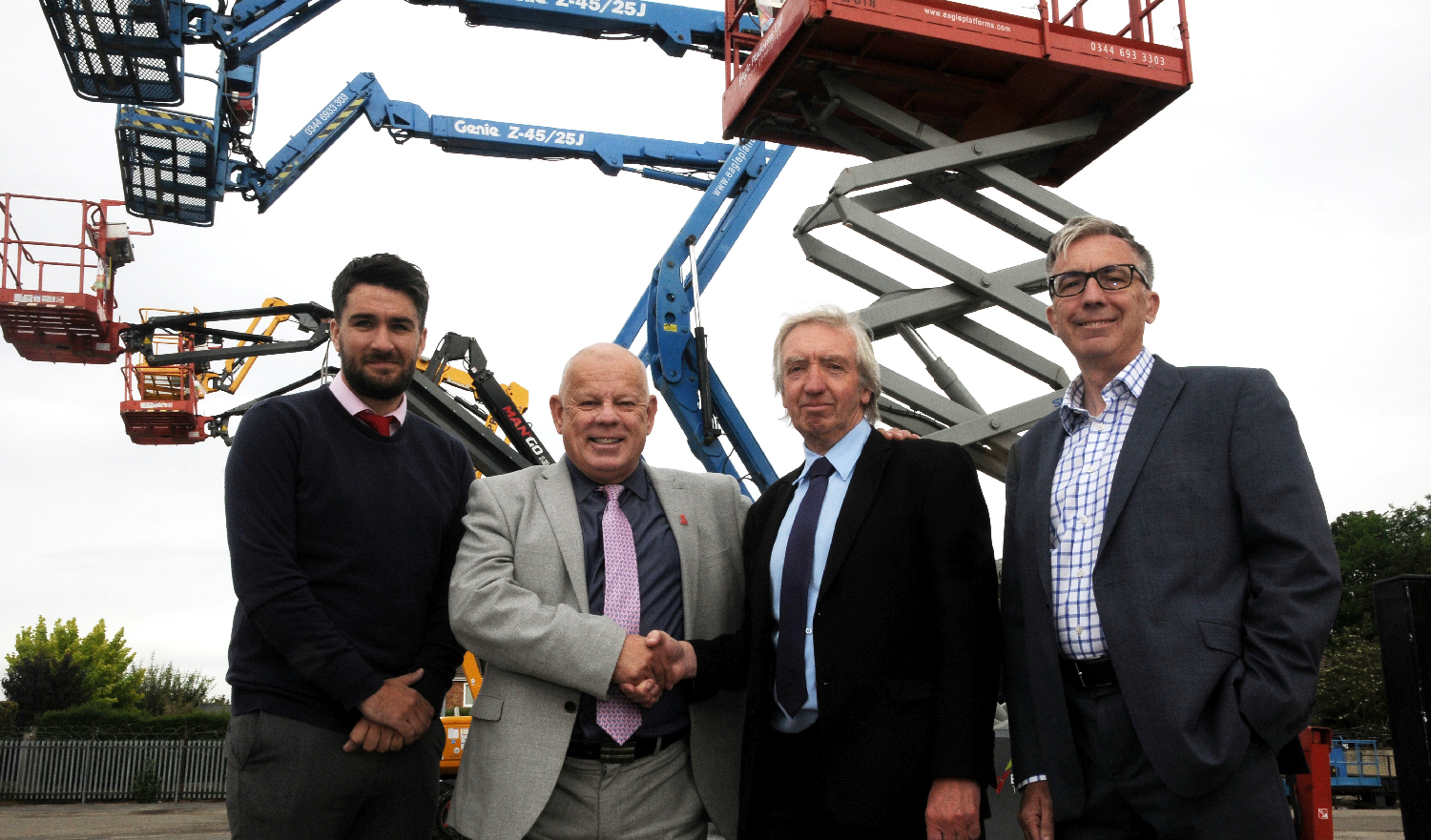 Four men outside standing in front of a large crane.
