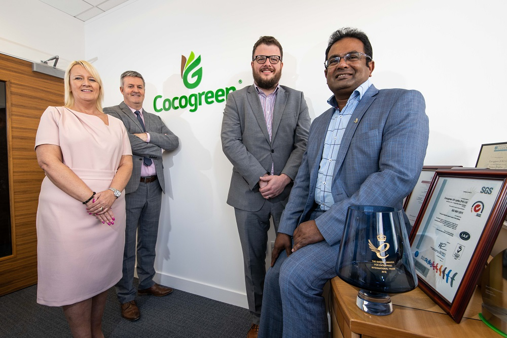 Group of four people in a office room standing in front of a wall with the Cocogreen logo. There is only one woman and she has blonde hair and is wearing a pink dress. There is an Asian man to the far right wearing a blue suit and a blue checked shirt. He is sitting on a desk surrounded by awards.