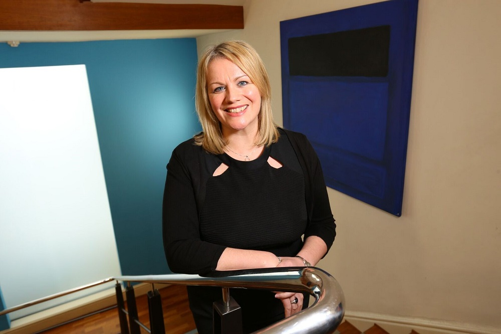 Joanne Whitfield, Fund Director at FW Capital stood on the stairs in an office building