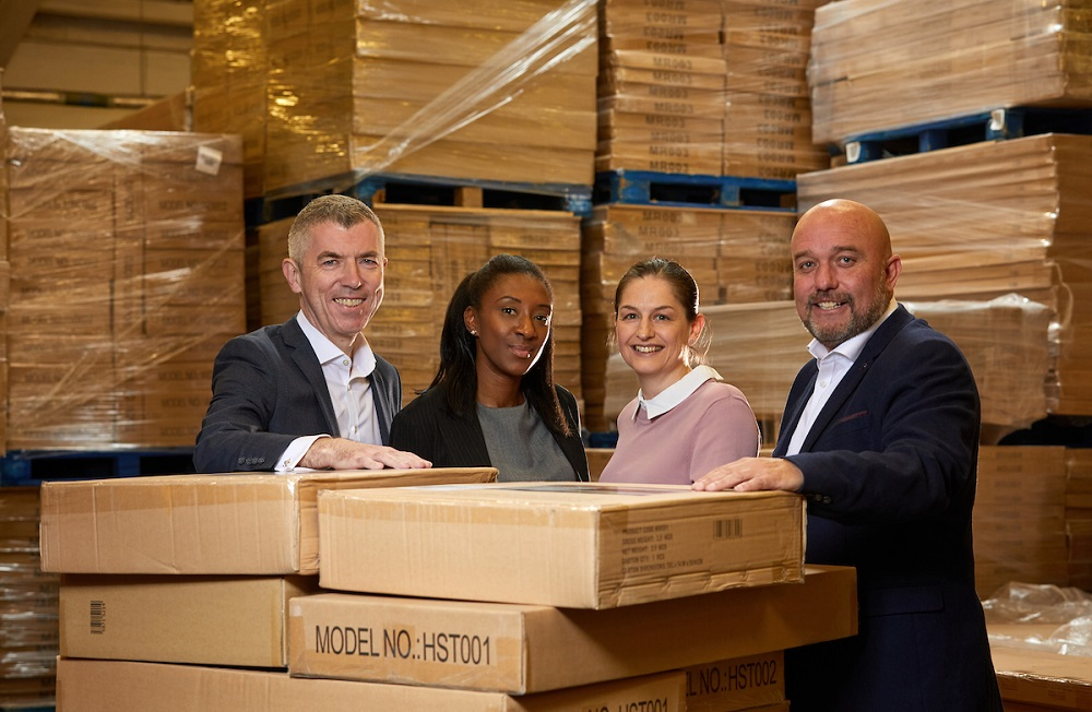 Two men and two women in a factory standing next to lots of cardboard boxes. Man to the far right is bald and has a beard, he is wearing a navy blue suit and white shirt, he is standing next to a lady wearing a dusty pink jumper, the next lady has dark skin and is wearing a black jacket and grey top and finally to far left there is a man wearing a black suit and white shirt.