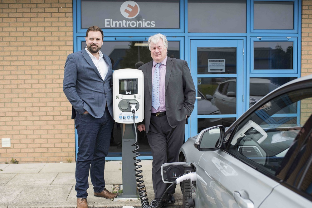 Two men standing behind building with Elmtronics signage. Man to the left is standing next to an electric charging post for vehicles is wearing a blue suit and white open necked shirt. He has a beard and dark hair. The man to the right has grey hair and is wearing a grey suit.