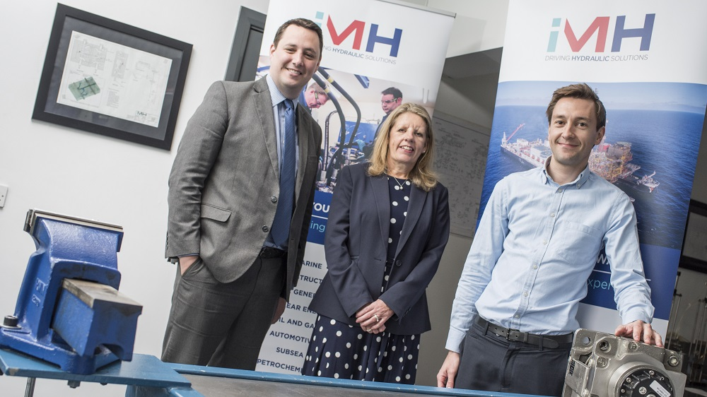 2 men and a woman stood in a meeting room with IMH Driving Hydraulic Systems pop up banners in the background