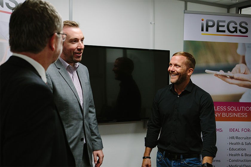 3 men from iPEGS talking in a meeting room with an iPEGS pop up banner in the background
