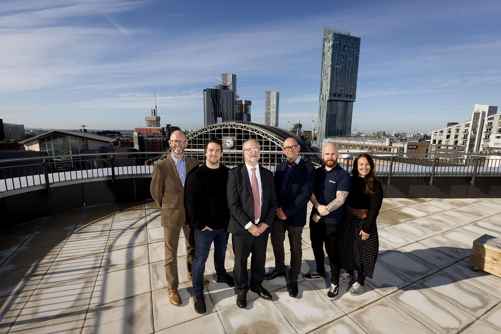 Employees from Node Technologies stood on a large balcony overlooking the city of Manchester