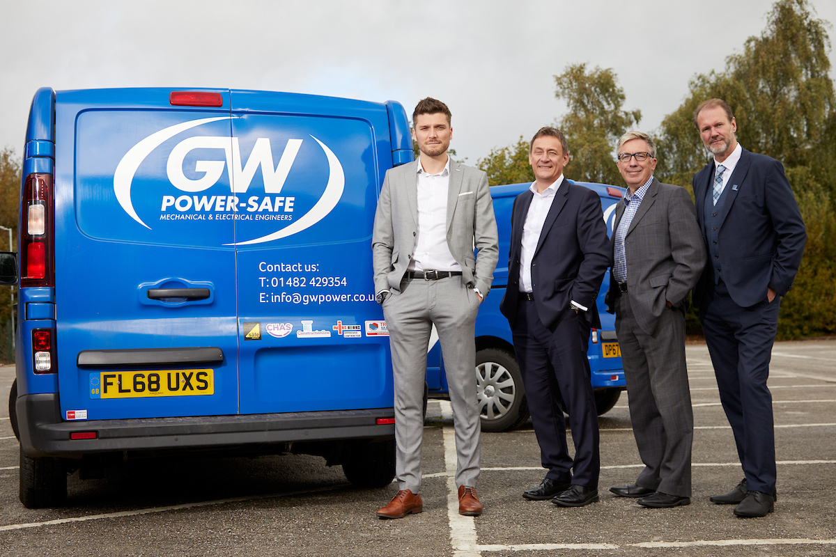 4 men in suits stood in a car park with 2 GW Power Safe vans