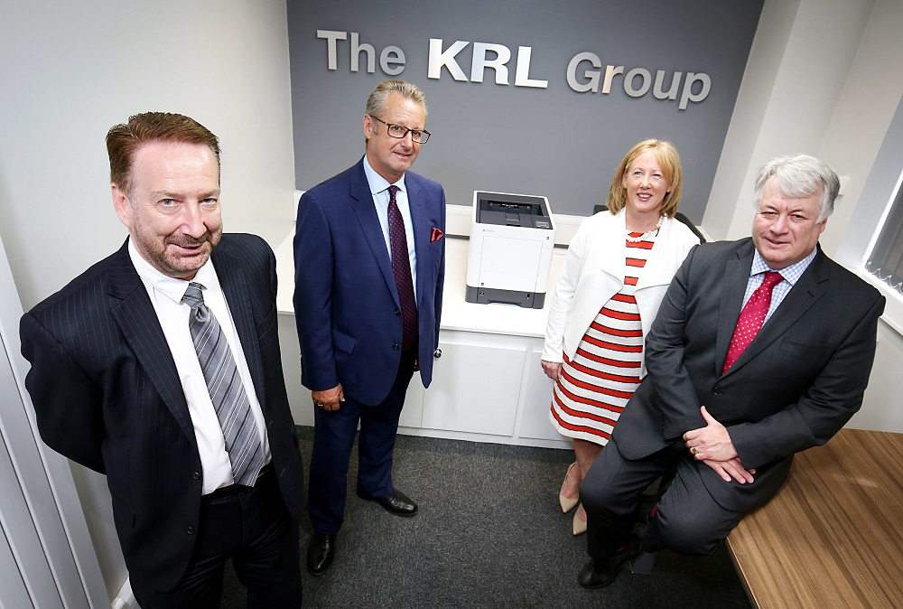 3 men and a woman stood in a small meeting room with The KRL Group sign on the wall in the background
