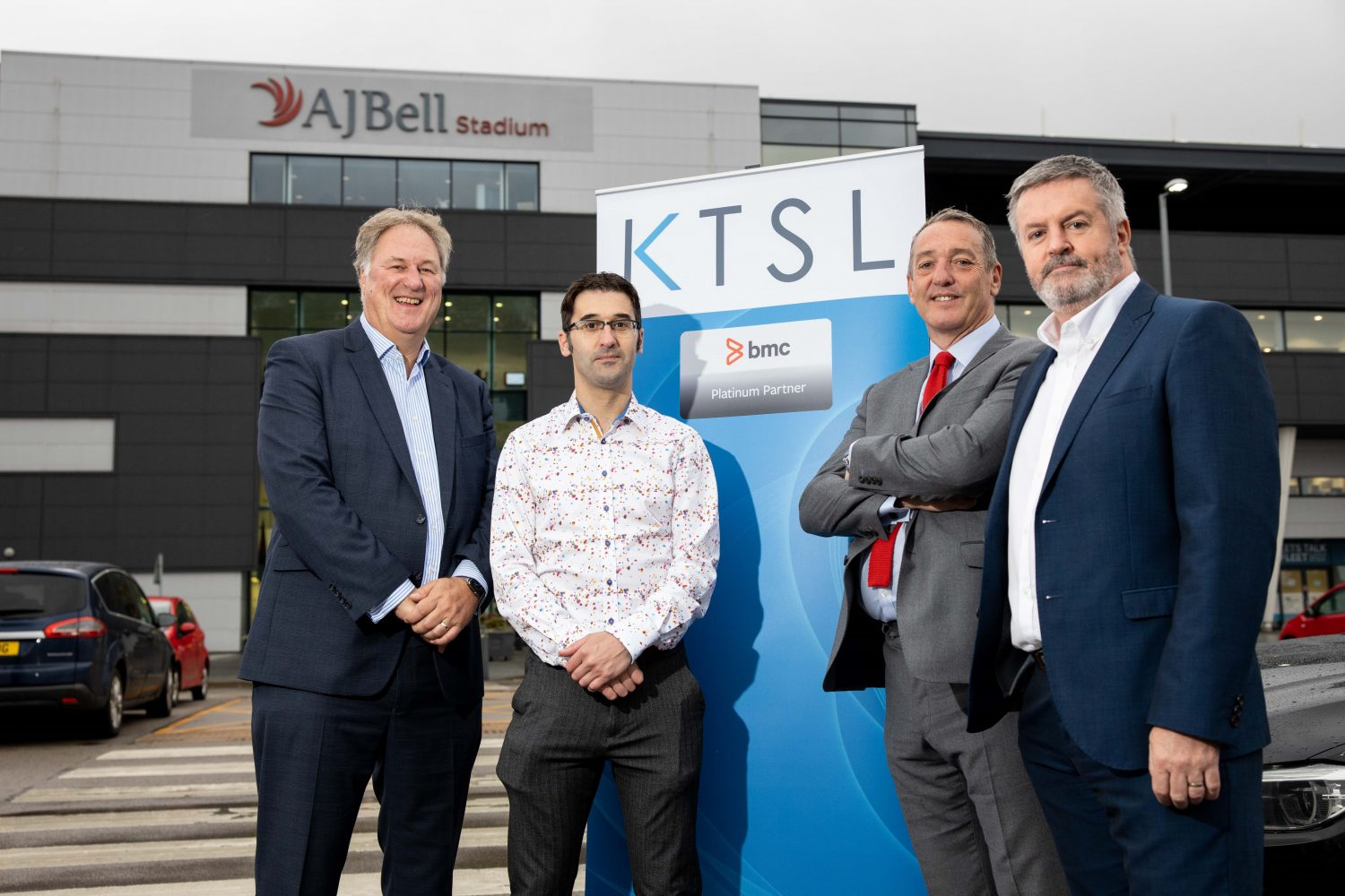 4 men stood outside of the AJ Bell Stadium with a KTSL pop up banner in the background