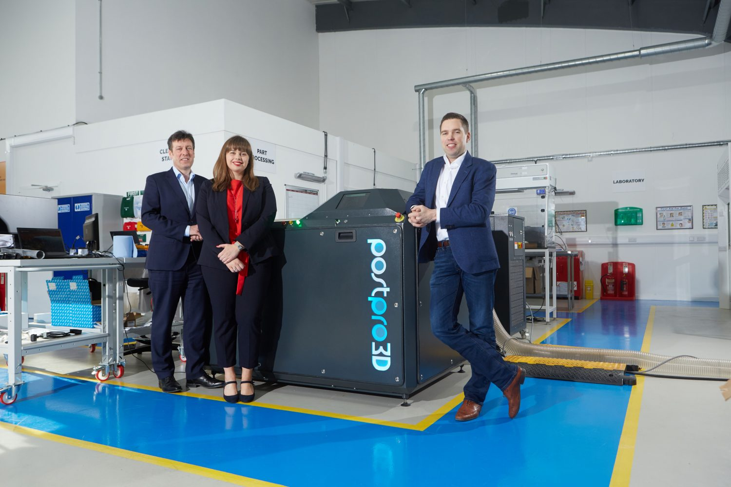 2 men and a woman from Additive Manufacturing Technologies stood next to a 3D printer