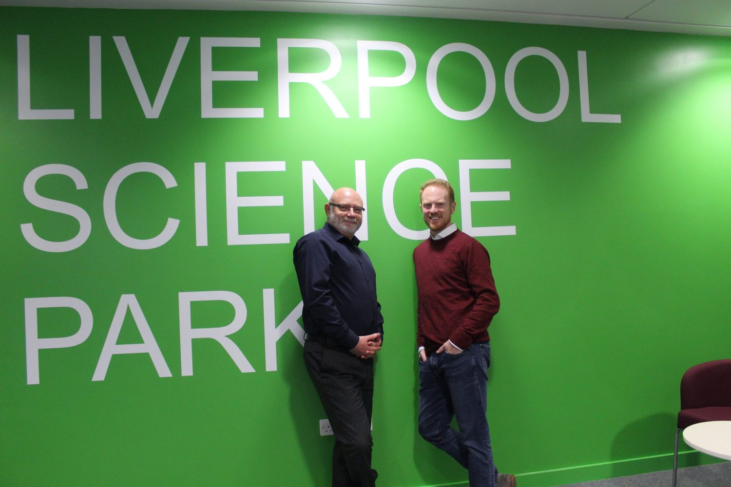 Two men standing in front of a green wall with white writing stating Liverpool Science Park. Man to the left has glasses andis wearing a dark blue suit and man to the right is wearing a maroon jumper and blue trousers.