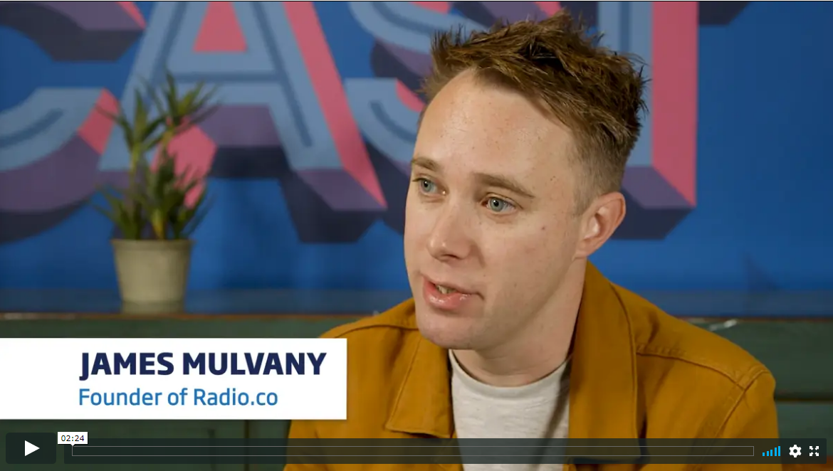 Young man sitting behind a colourful wall is wearing a mustard yellow jacket and a beige sweat shirt. He has blue eyes. He is named James Mulvany and is the founder of Radio.co