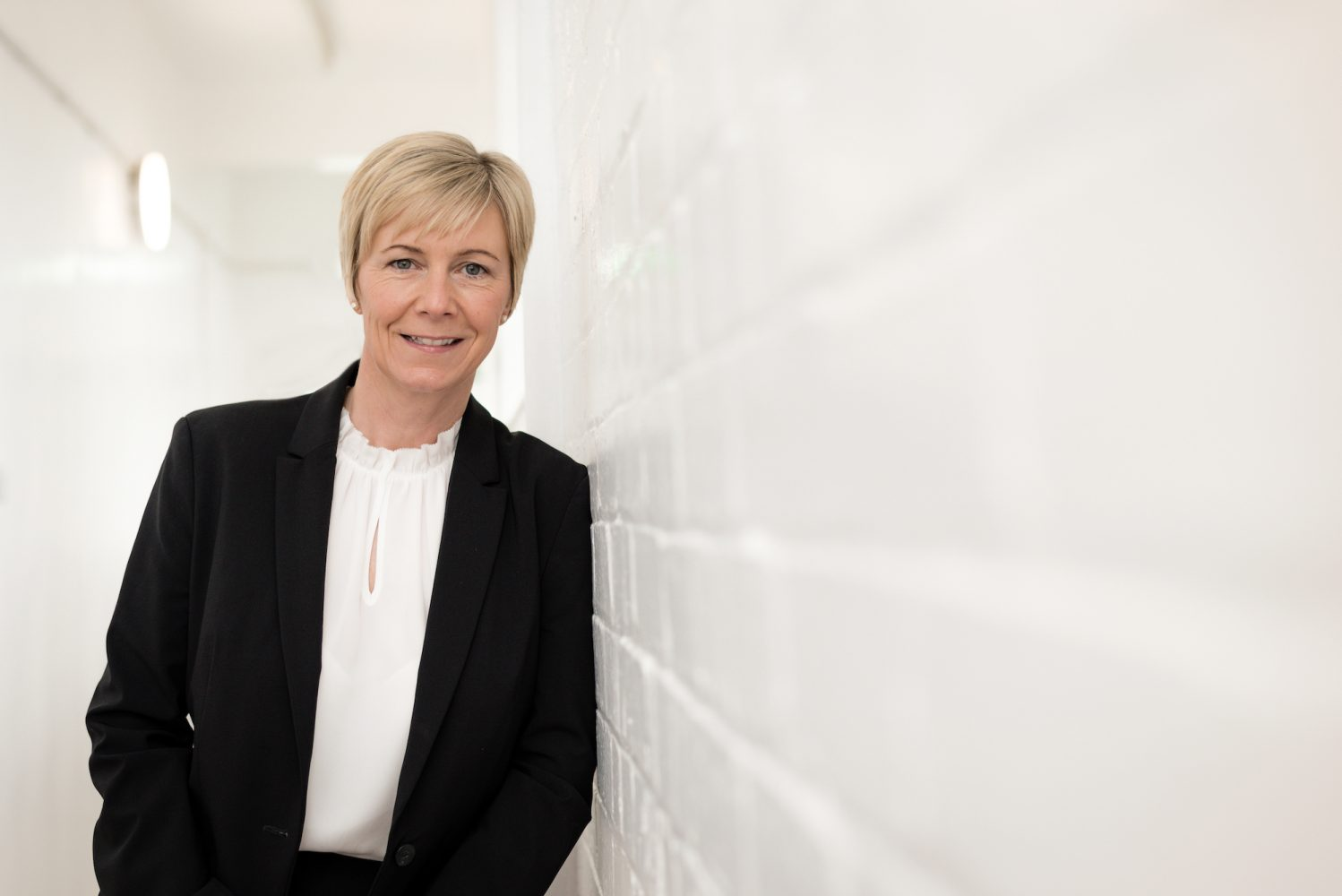 Lady with short blonde hair wearing a black jacket and a white shirt leaning against a white brick internal wall.