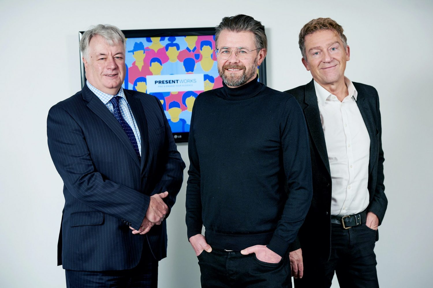 Three men standing in front of screen showing Present Works on the screen. Man to the far left is wearing a black suit with a white shirt, man in the middle has a beard and is wearing a black jumper and black trousers and man at the far left has grey hair and is wearing a blue suit, a checked shirt and blue tie.