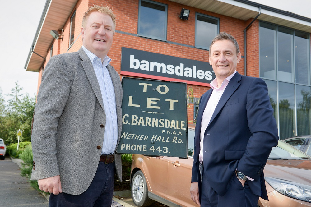 Two men standing outside office with Barnsdales signage on building. Man to the far right is wearing a blue suit with a pink shirt and taller man to the left is wearing a grey jacket, blue shirt and a navy trousers.